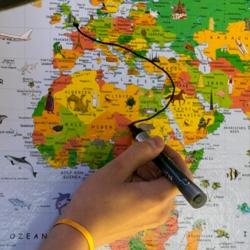 Mit einem Stift wird auf einer Weltkarte gemalt
